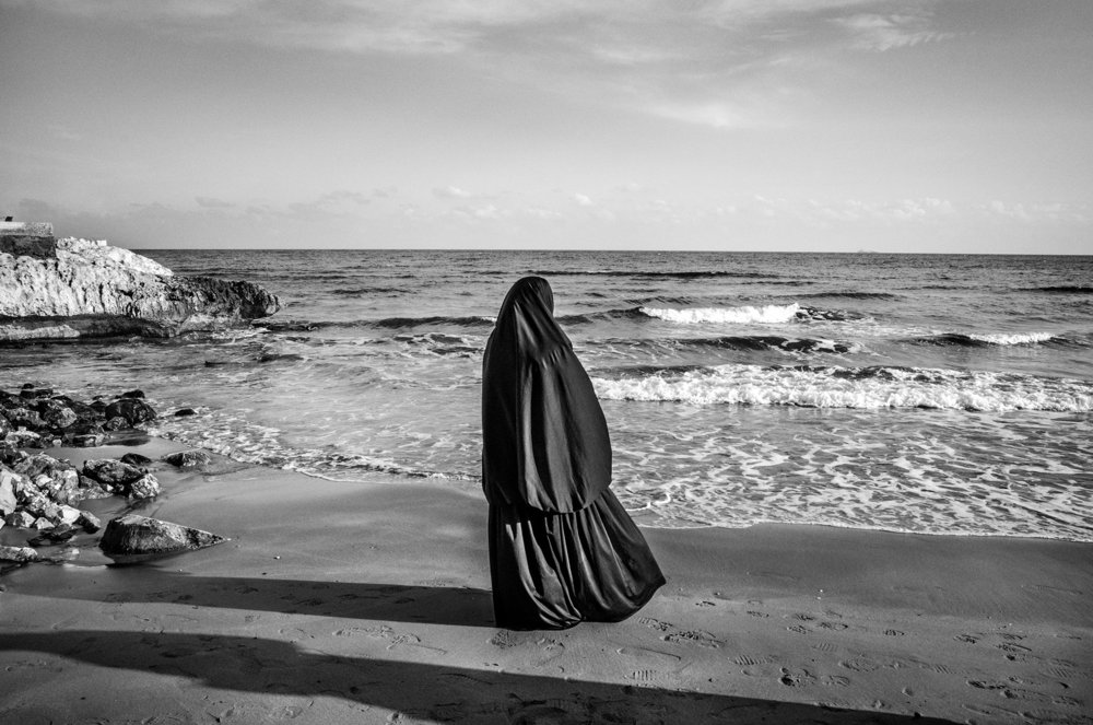 Kiz Kalesi, Turkey - A Syrian woman in Kiz Kalesi near Mersin, Turkey, looks at the sea waiting to board an illegal ship for Europe. As the Syrian civil war continues with no end in sight, thousands of Syrian refugees have reached the Turkish coasts around Mersin, turning to human smuggling operations as a way to reach Europe. One of the smugglers operating out of the port of Mersin, when interviewed in 2015, reported that $6,000 (USD) are required, per person, to get illegal passage to Europe on board of old freighters.