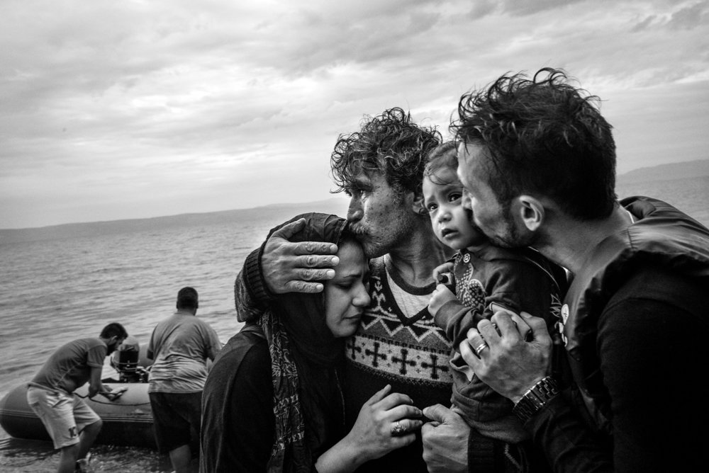 Skala Sykaminias, Greece - A Syrian family weeps tears of joy after reaching, on a rubber boat from Turkey, the village of Skala Sykaminias located on the northeastern Greek island of Lesbos. Thousands of refugees, mostly coming from Syria, Iraq and Afghanistan, have crossed the Aegean Sea from Turkey to reach Europe: a relatively short but extremely perilous journey. According to the UN Refugee Agency, more than 850,000 arrivals by sea were registered in Greece in 2015.