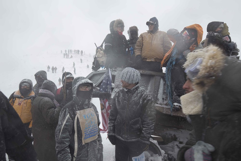 "Water Protectors and veterans from Oceti Sakowin protest camp gather along highway 1806 on December 5, 2016 during an ""unsanctioned"" protest action, spurred by veterans who arrived the day before."