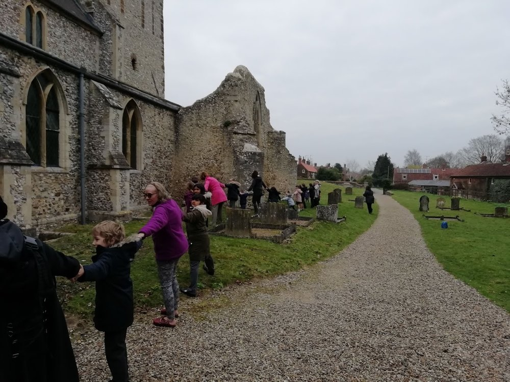 Flitcham pupils clypping the church. 2019  Sandringham and West Newton school held their annual Mothering service at West Newton church on the 29th March. It was a lovely sunny morning. After a short service in church everybody went outside for the clypping of the church. This is a medieval custom at which everyone holds hands and makes a loop around the church in order to show our love and respect for mother church. With parents and staff members as well as the children, we were easily able to completely surround the church! we then have 3 cheers for the church. The service finishes with prayers in the churchyard.  Flitcham school did their service on 28th March. Sadly, they weren't so blessed with sunny weather. Flitcham church is much larger so it was a real stretch but we managed it there as well!