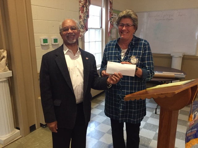 Louise Theberge, Gloucester-Mathews Care Clinic Board of Directors President receiving a check from Gloucester Point Rotary Club President, Ron Saunders