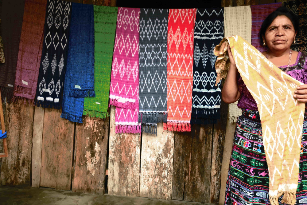 A woman at the San Juanera cooperative displays original scarves made on the backstrap loom.