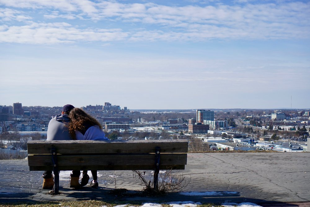 A couple enjoys a winter break atop Munjoy Hill, taking in the view from Ft. Sumner Park. A proposed residential development on Sheridan St. would obstruct a large portion of the unique vista.