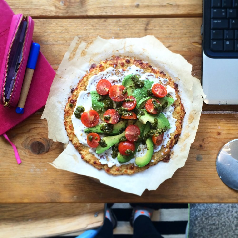 Cauliflower crust pizza with avocado, creme fraiche and herb oil