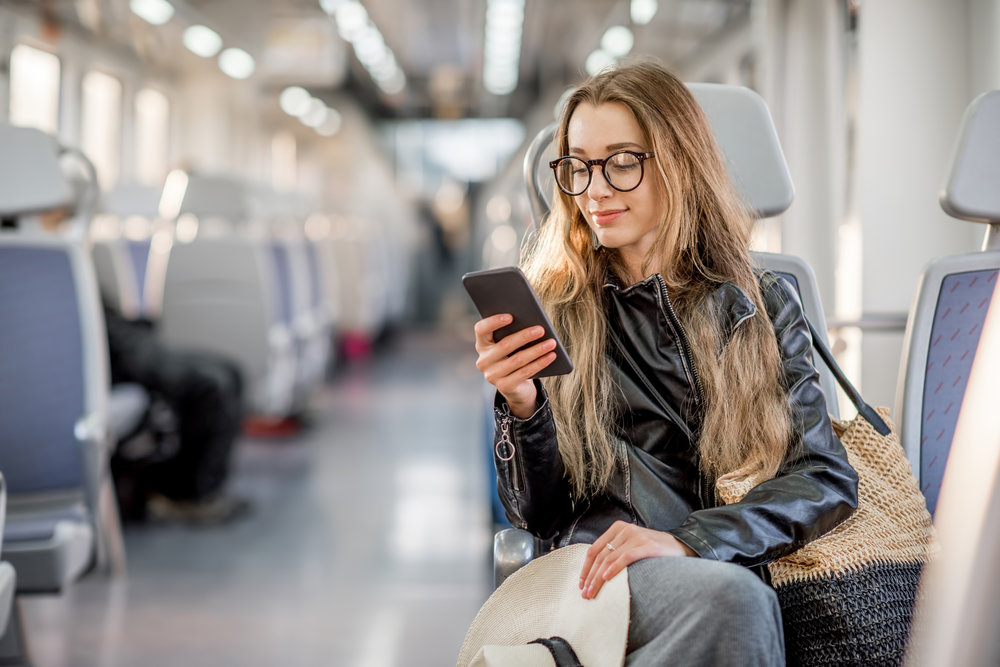 girl on her phone on a train