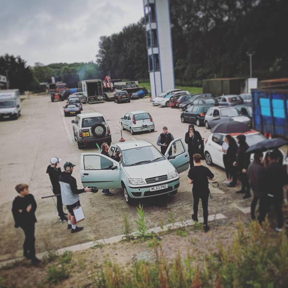 Stuntmen and student filmmakers shooting car scene