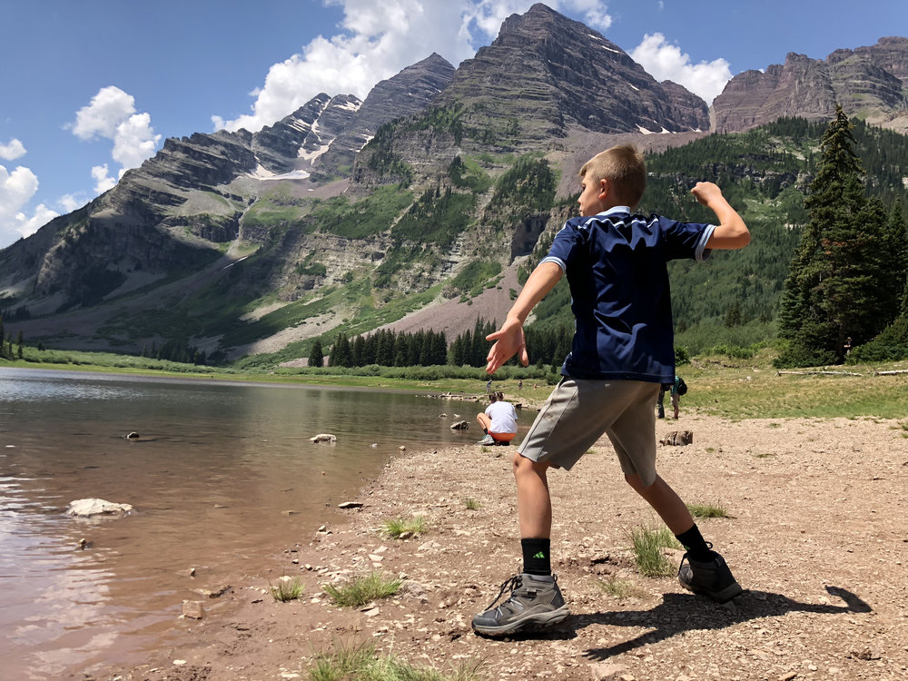 boy-skipping-rocks-crater-lake-maroon-bells