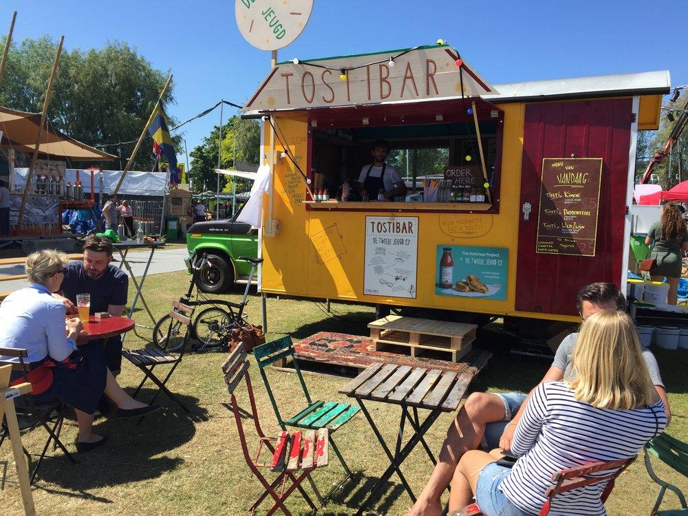 De festivalwagen trekt deze zomer rond. Hij is ook beschikbaar voor catering en evenementen. Interesse? Laat het ons weten met een mailtje naar tostibar@detweedejeugd.nl