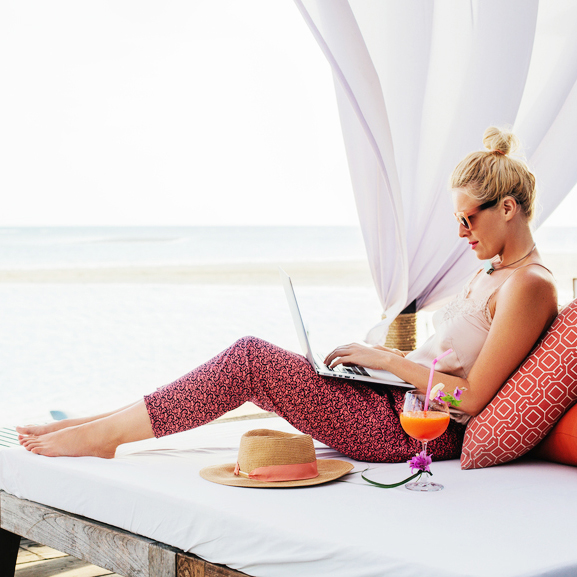 Woman With a Laptop in a Beach Lounge Bar