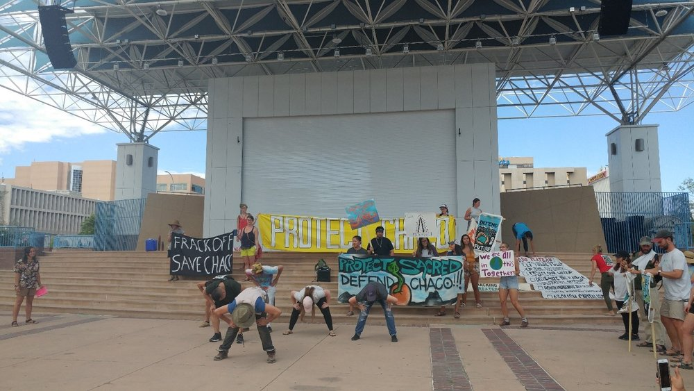 Uplift protesters gather around to watch a dance prepared for a rally at Albuquerque Civic Plaza Sept. 16, against fracking on Greater Chaco. This display stresses the importance of art for Uplift in the fight for climate justice. (Photo Credit: Gabriella Johnson)