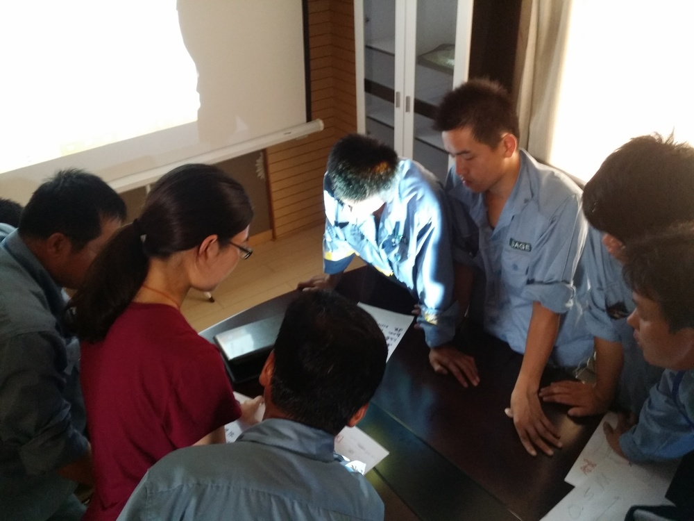 The next generation of  Chinese LDAR technicians huddling around an Ei tablet during a LDAR training session.