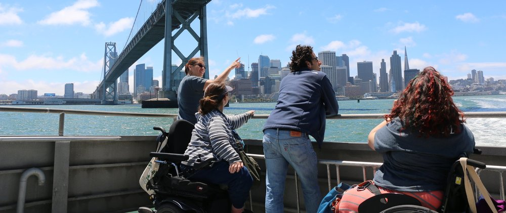A group of people rides a ferry under the Bay Bridge.