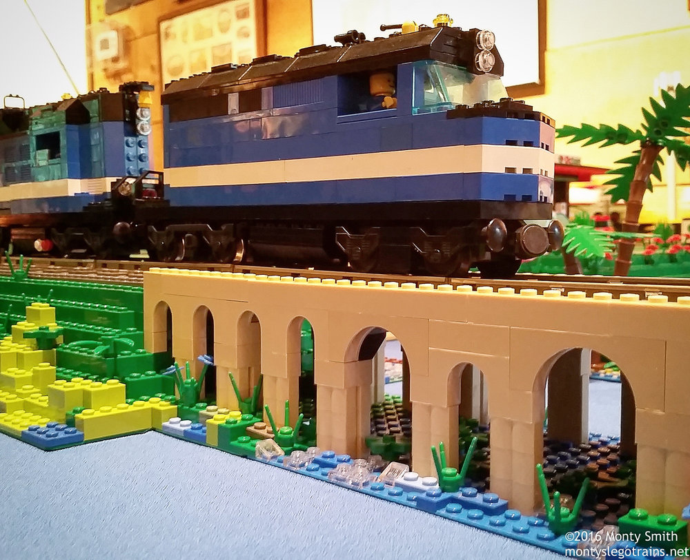 An F40PH leads a passenger train over an arched bridge on my Lego train layout at the FSRM Labor Day train show.