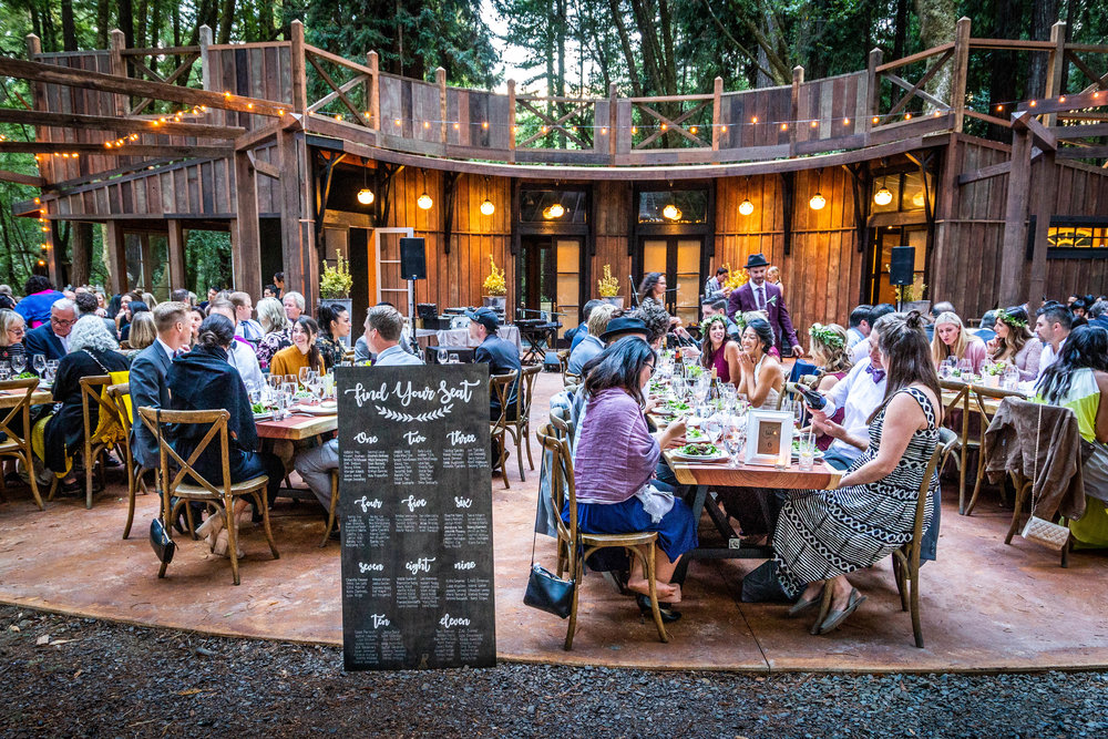 Wedding guests seated at wooden tables at the Redwood Pavilion at The Brambles in Philo, Anderson Valley, California