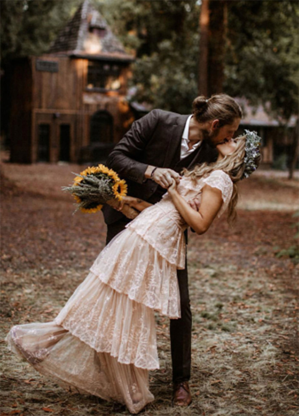 A bride and groom kiss in front of the main accommodations in the Burly Grove at The Brambles outside of Philo, California in Anderson Valley
