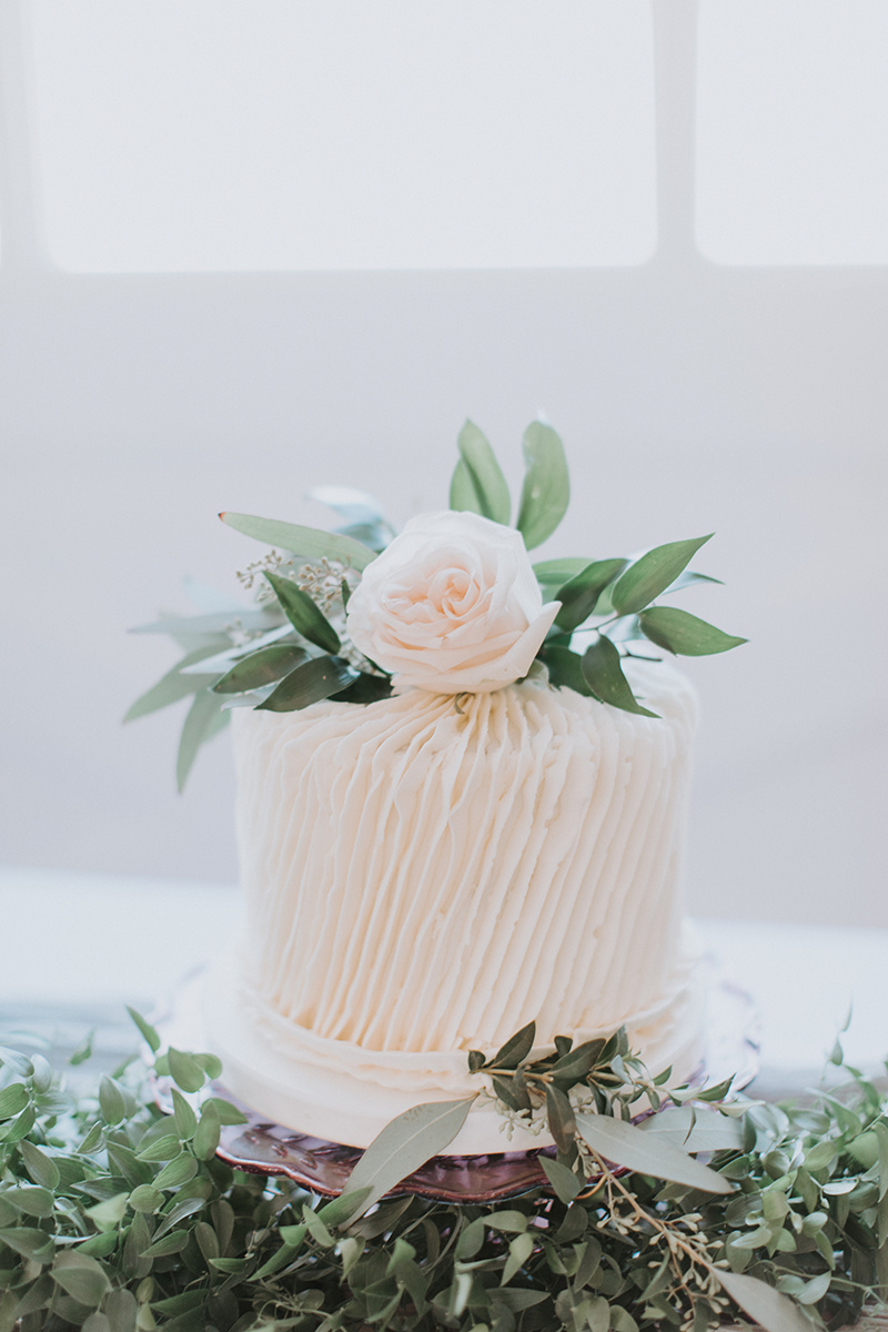 Winter wedding cake with greenery by Sweet Crumbs. Photo by Alex Lasota