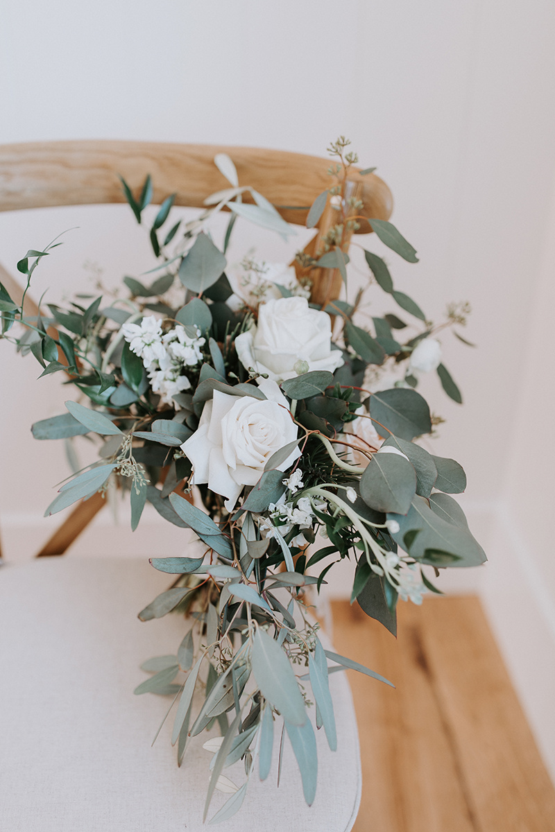 Bridal bouquet for winter wedding with eucalyptus and olive leaves by Fleur De Lis. Photo by Alex Lasota