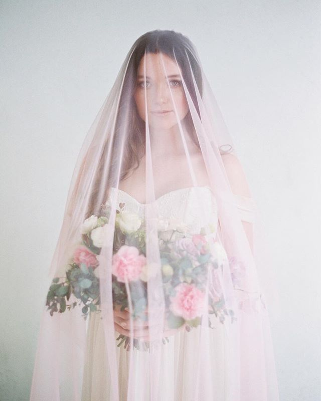 Double tap if you'd wear a pink veil.💖 I know it's not the traditional color but I love how romantic and soft the Rose Veil is especially gently draped against this gorgeous bouquet from @thebloomingbud! ⠀⠀⠀⠀⠀⠀⠀⠀⠀ ⠀⠀⠀⠀⠀⠀⠀⠀⠀ Photo by @mallorydawnphoto  Featuring the Rose Veil💕 Hair and makeup by @nicol_artistry  Dress by @jillianfellersbridal  Florals by @thebloomingbud  Vintage rentals @sweetsalvagerentals  China and Tableware @sundrop_vintage  Calligraphy by @alleyandco  Rings @trumpetandhorn  Model @kdonovan101 Featured on @stylemepretty ⠀⠀⠀⠀⠀⠀⠀⠀⠀ ⠀⠀⠀⠀⠀⠀⠀⠀⠀ #pink #veil #bridalveil #pinkveil #stylemepretty