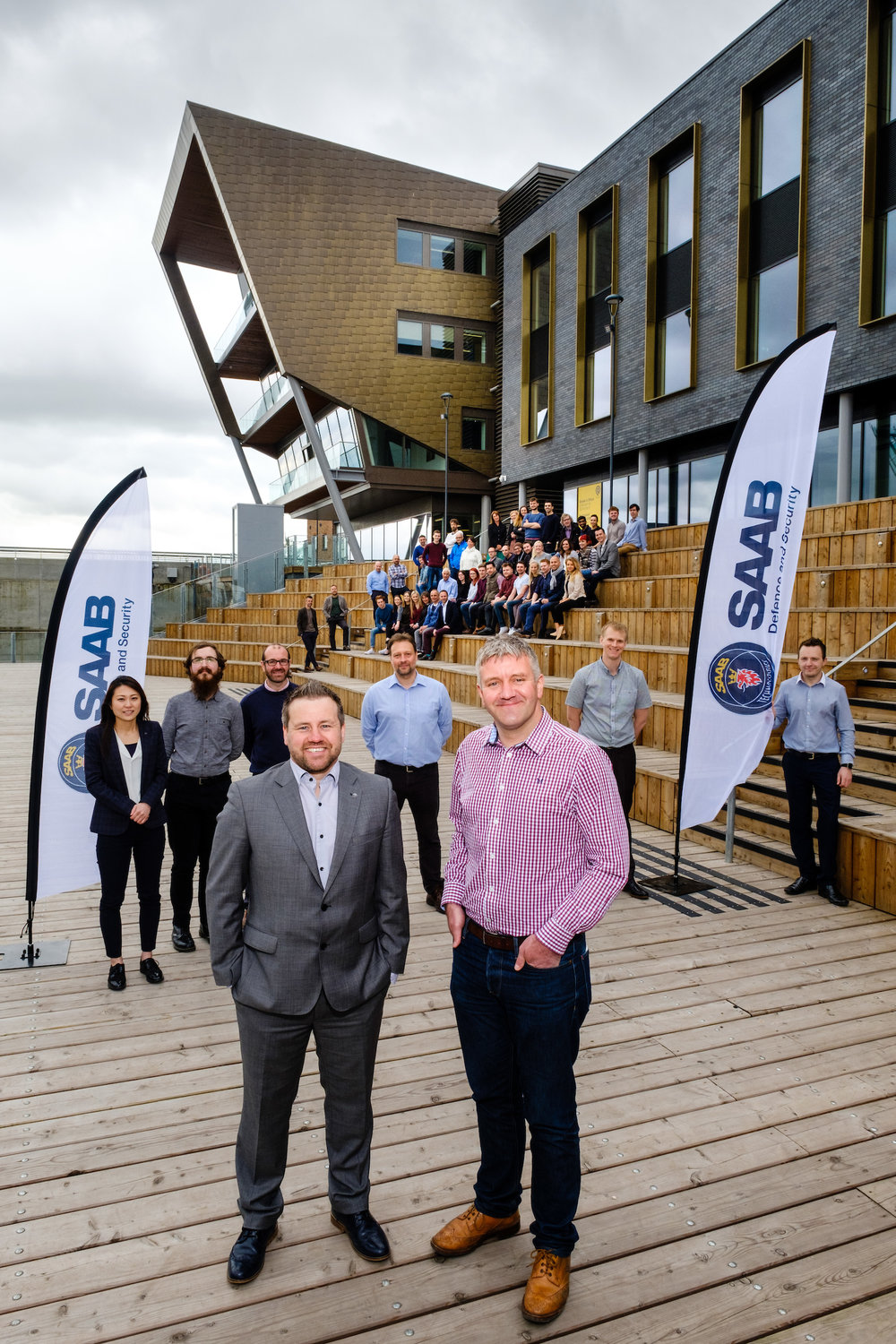 C4DI Managing Director John Connolly, right, welcomes Simon Read, UK Director of the Networks and Public Safety business unit of global technology company Saab, and his colleagues to the Hull tech hub. They are pictured in the Stage@TheDock amphitheatre within the @TheDock development of which C4DI is the centrepiece, with other members of the C4DI community.