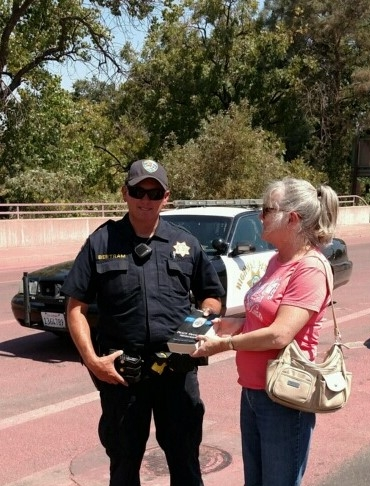 "Elaine giving POM Bible to California Highway Patrol Officer Bertram at Clayton Fire.  Note pavement: Fire plane dropped retardant on California Highway Patrol car parked close to the fire shortly after I left, ducking both flames and planes.  Firefighters call this getting ""snotted on."""