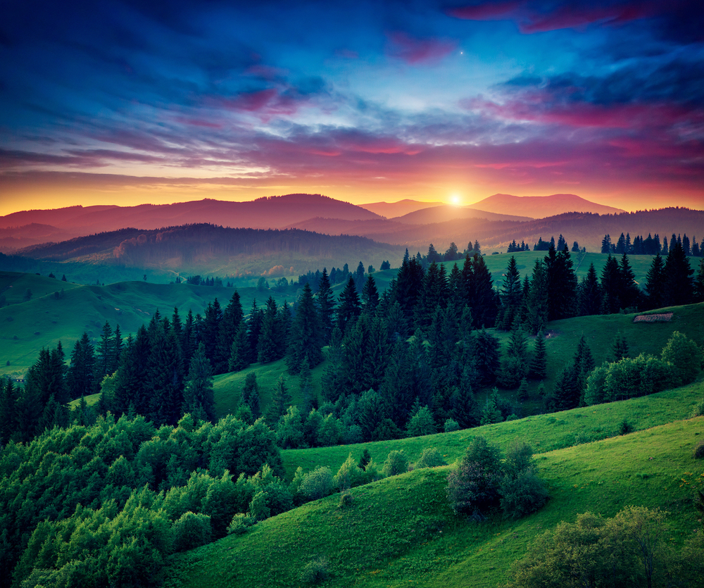 Green hills glowing by warm sunlight at twilight. Dramatic scene. Colorful sky, red clouds. Carpathi