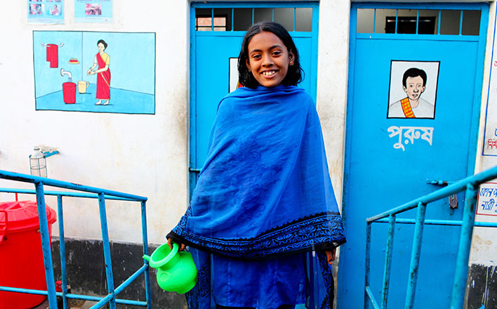 Twelve year old Lima outside the latrine block in Kalshi Takar Baa slum, Dhaka, Bangladesh. Photographer credit: WaterAid/GMB Akash/Panos.