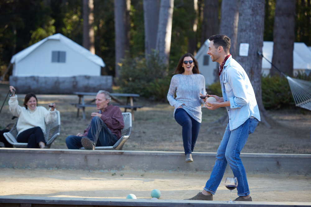 A group of happy campers play bocce