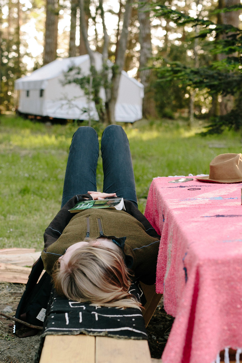 A young woman rests on a picnic table bench with open book on her belly.
