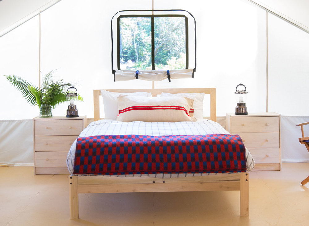 California glamping at its best — a comfortable full bed in our Classic Tent with oil lamps on bedside tables