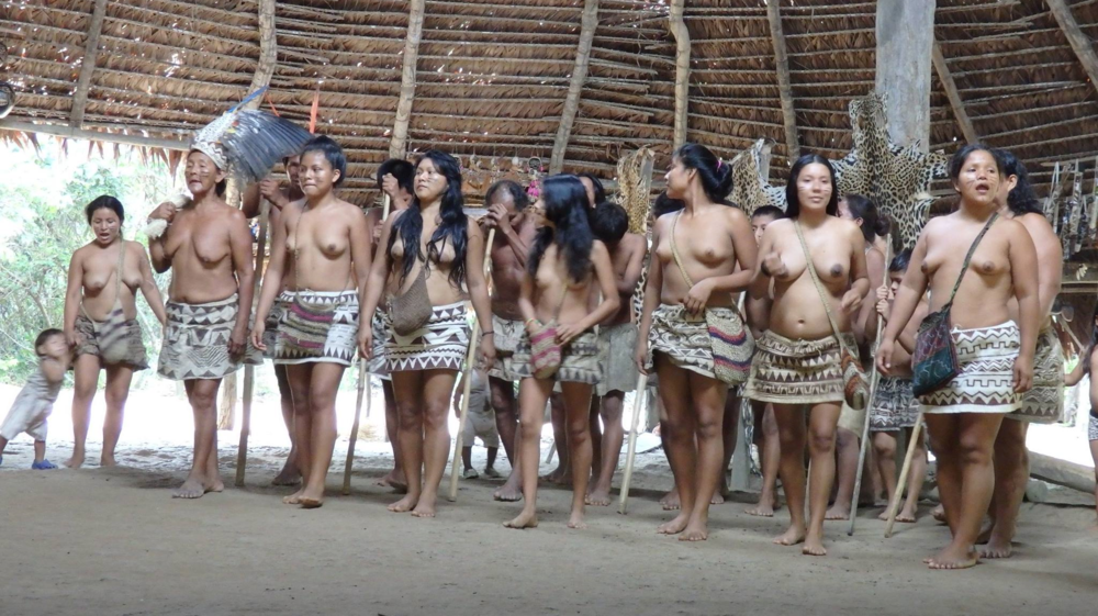 Women of the Bora tribe inside their maloca. Jaguar pelts strung up in the background. Photo: Melanie Crandall