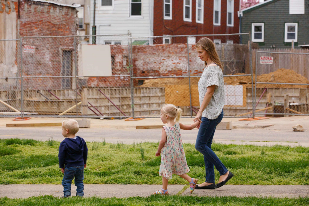 Jana Curtis and two of her children walk past one of many construction sites in their river ward neighborhood. Three-year-old Nolyn Pace, center, was poisoned by lead in the soil in their backyard