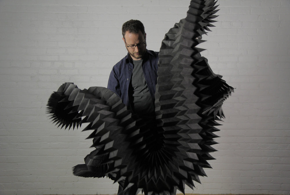 Matthew Shlian, seen here with his work.