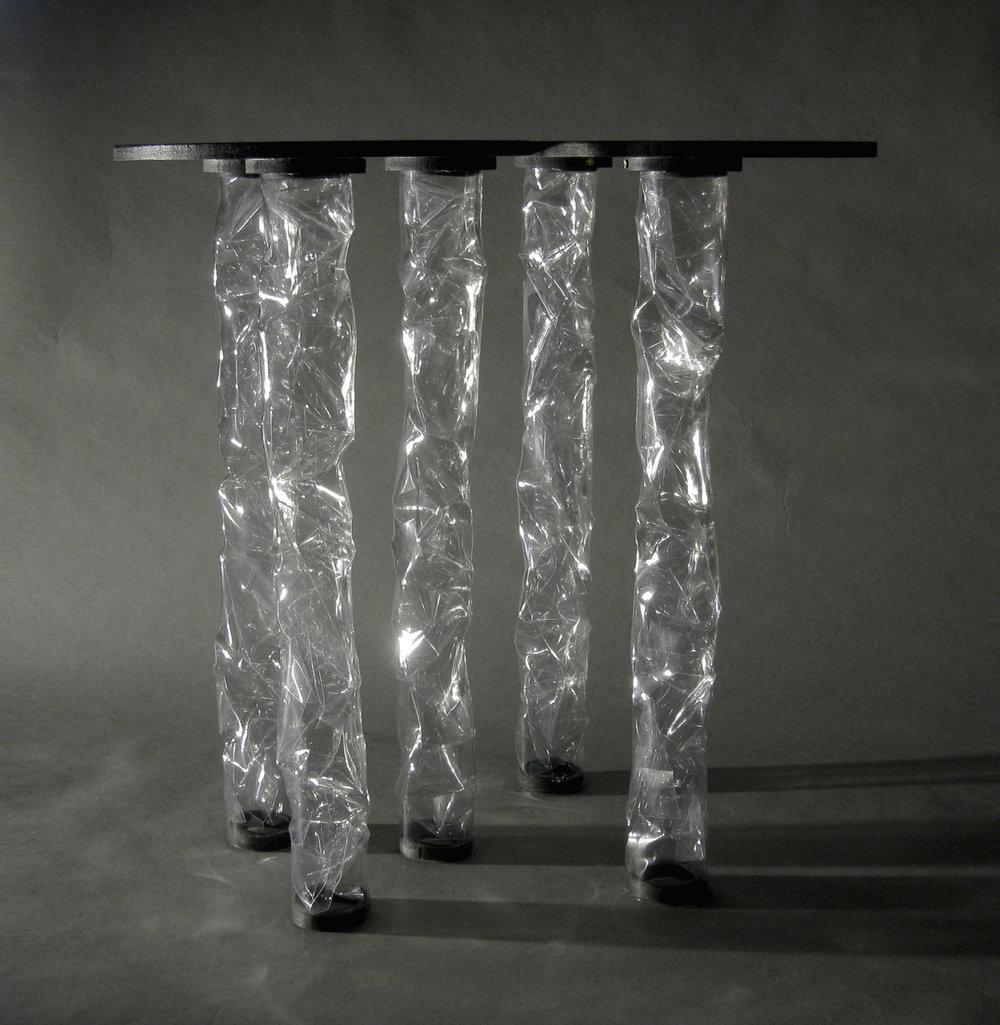 im Wald  is a series of side tables by Taeg Nishimoto, made of transparent legs of two types of plastic (heat-resistant polyester sheet, and heat-responsive PETG tubes) and a combination of differently sized disk tops in black. It is an exploration into the making of visual as well as tactile textures from transparent plastic and their effects.