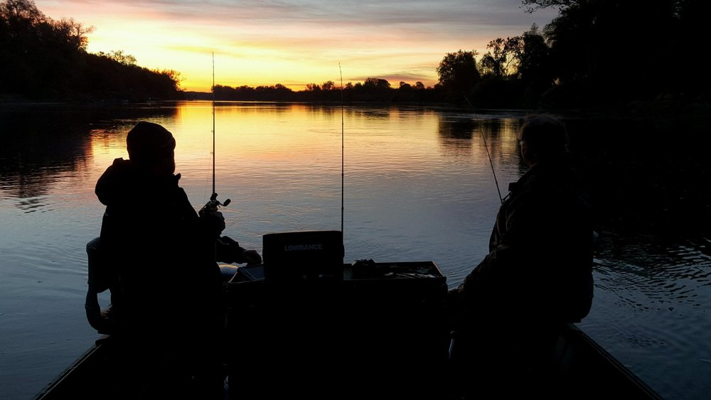 SalmonSacRiver.com  salmon fishing guide Mike Rasmussen enjoys a sunrise on the Sacramento River with his father Richard Rasmussen from Dairyville, Ca while the father and son fish for Late Fall Run Chinook Salmon at Woodson Bridge near Corning, Ca. This photo was taken in December of 2015.  Mike's Fishing Guide Service for Northern California salmon fishing guided adventures, and Sacramento River Fishing Guides. Targeting Sacramento River Salmon, Sacramento River Striped Bass, White Sturgeon on the Sacramento River, American Shad And Rainbow Trout, The Best Sacramento River Fishing Guide and Sacramento River Salmon and Striped Bass Fishing Guide On The Sacramento River. Sacramento River Fishing is our specialty.