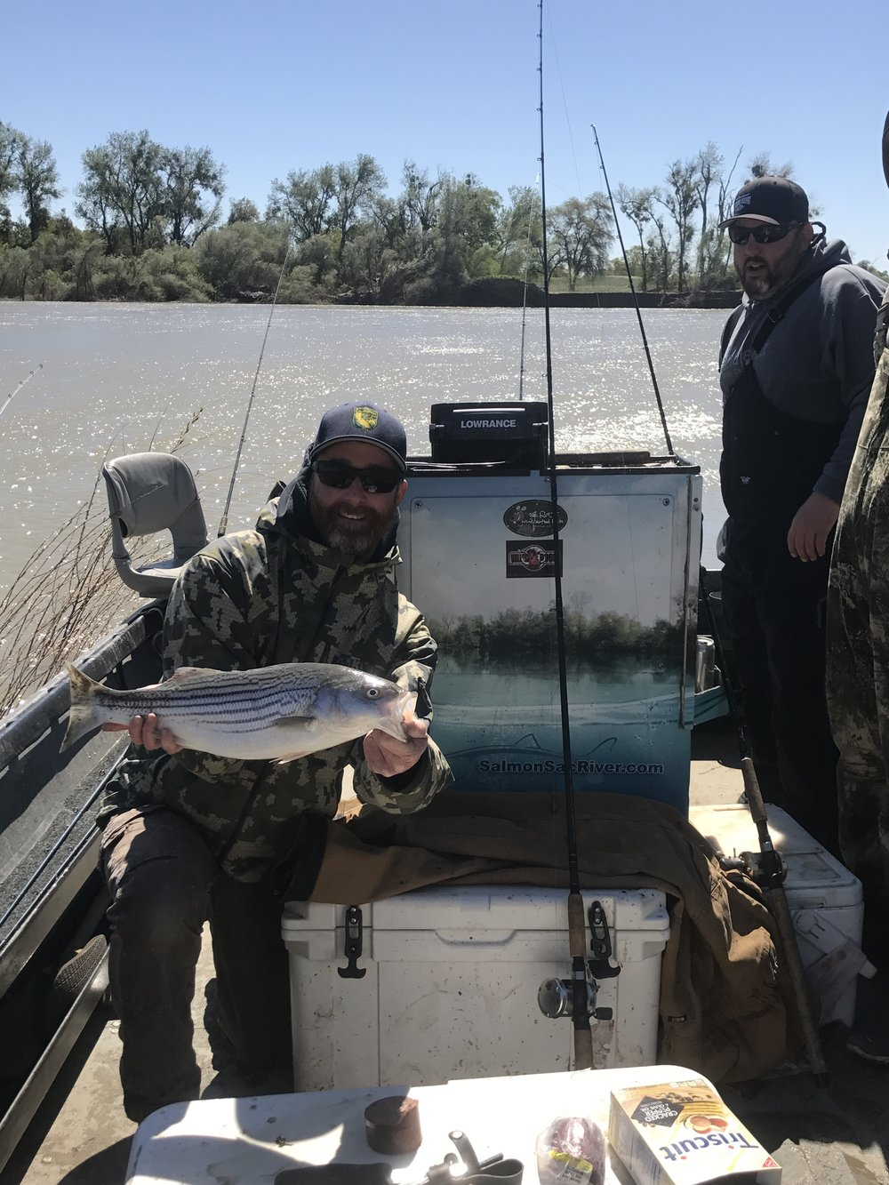 John Paterson from Corning, Ca holds up a quality striped bass he caught while on a two day alcohol induced bachelor party for Kevin Barnes (pictured on right of photo) of Corning, Ca on April 31, 2017. A very present wind chop can be seen on the river in the back ground.