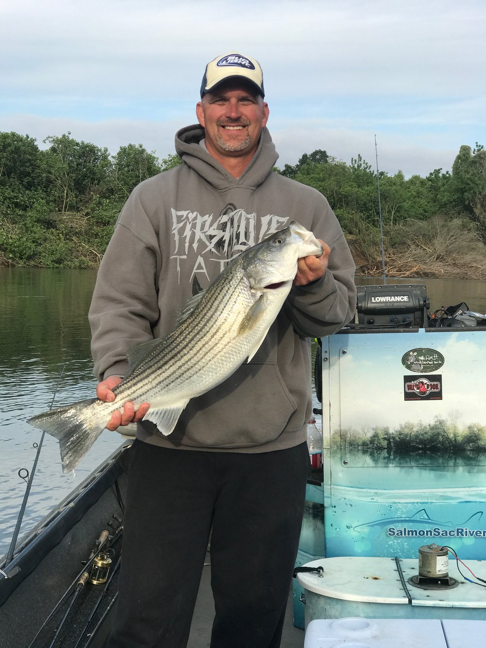 Chris Olson from Anderson, Ca holding a double digit striped bass he caught on the Feather River with striped bass fishing guide Mike Rasmussen of  SalmonSacRiver.com .