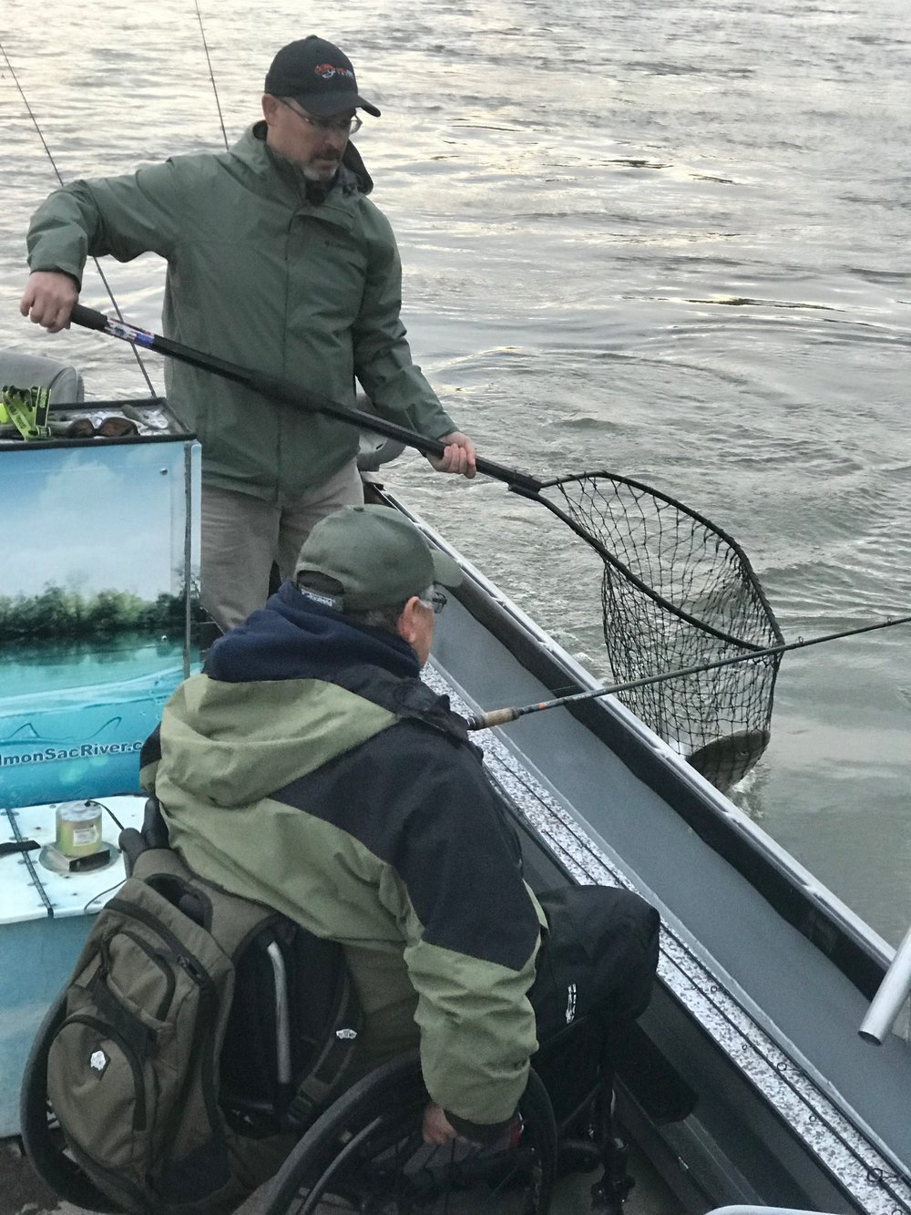 Craig Newton, owner of Will Fish Tackle, in Auburn, Ca (  willfishtackle.com ) helps fishing guide Mike Rasmussen and nets a quality striped bass, caught on a live minnow.