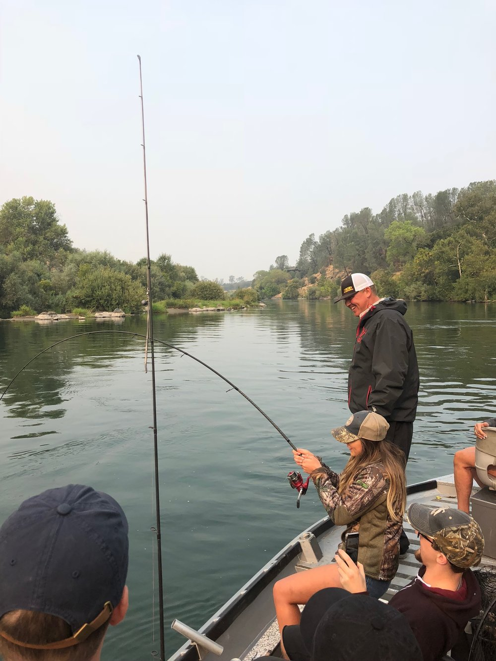 Angler Kyle keeps a tight grip on her Phenix Trifecta as she does battle on the Sacramento River in the canyon region near Red Bluff, Ca on August 25, 2018. Johny Eller stands by as Kyle's group takes pictures and cheers her on during her battle!
