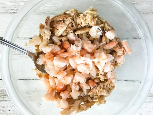 Lump crab and chopped shrimp in a glass bowl with a spoon