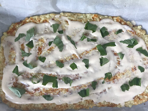 flatbread pizza topped with alfredo sauce and chopped basil