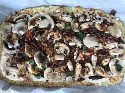 flatbread pizza topped with mushroom, chicken, tomatoes, capers, bacon, and chopped herbs prior to going into the oven.