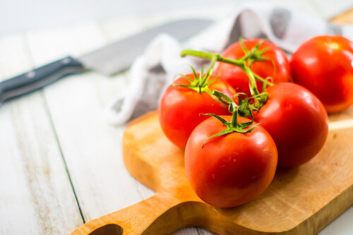 Vine ripe tomatoes on a wooden cutting board.