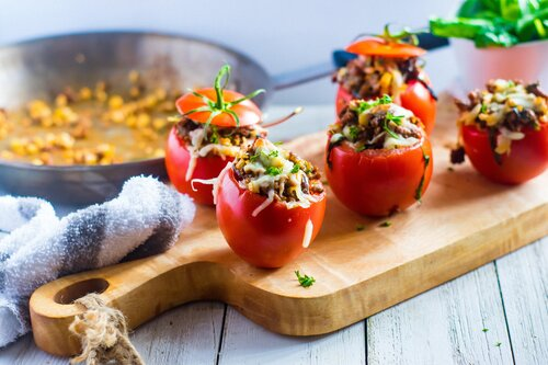 Spicy Stuffed Tomatoes on a wooden cutting board.
