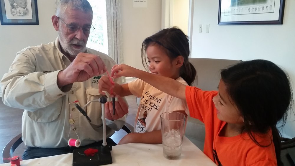 """Master fly tyer Len Ruggia works with some of the Black Oak kids to make some """"Red Leech"""" pattern flies. The kids fished these later in the afternoon and caught ALOT of fish."""