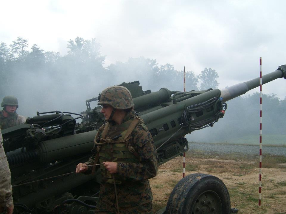 """Marine Corps Officer, Sallie Benson about to pull the string that makes the howitzer go """"boom."""""""
