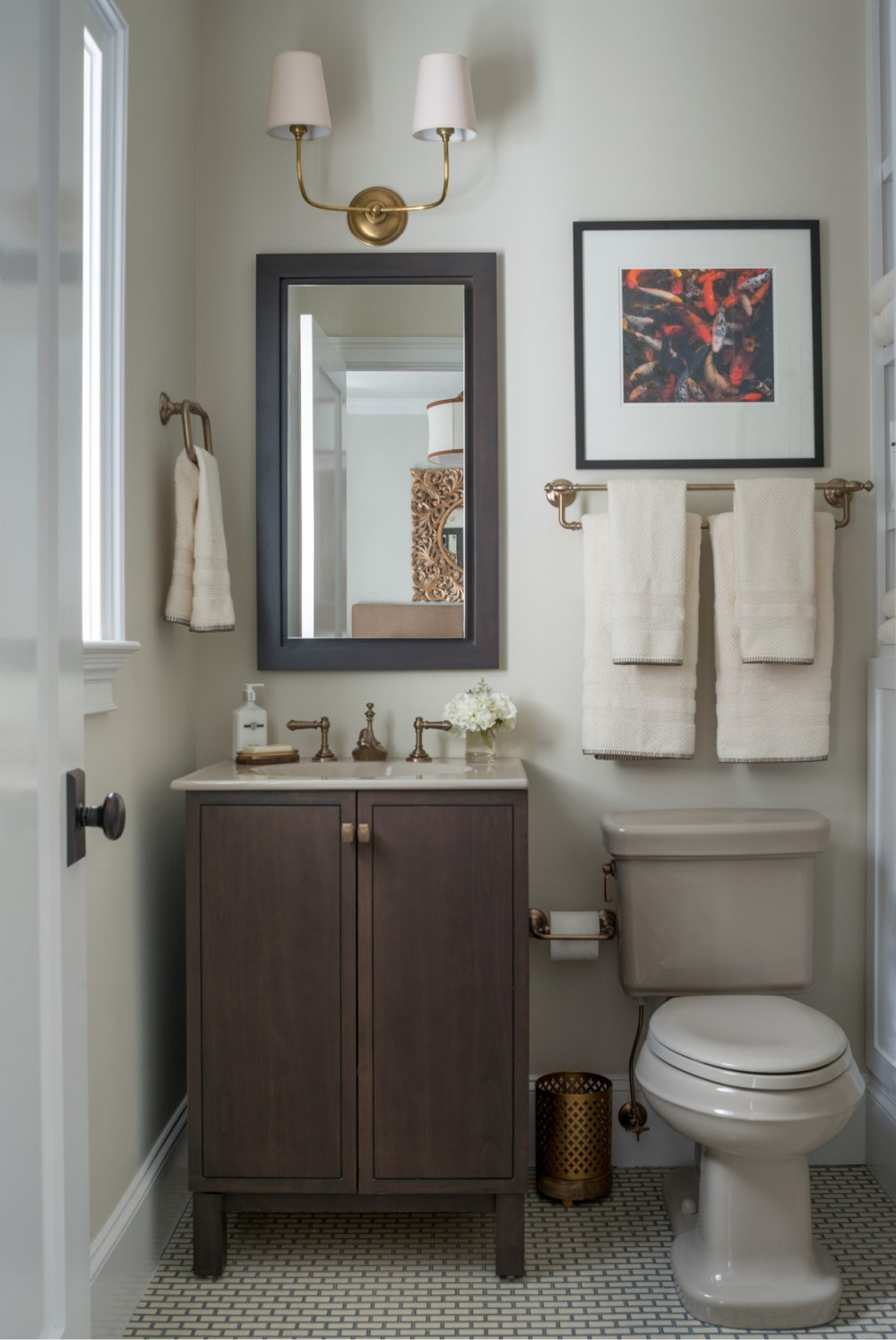 The second-floor guest bath's palette echoes nature's hues, with sand-colored fixtures, warm bronze faucets and a dark wood vanity.