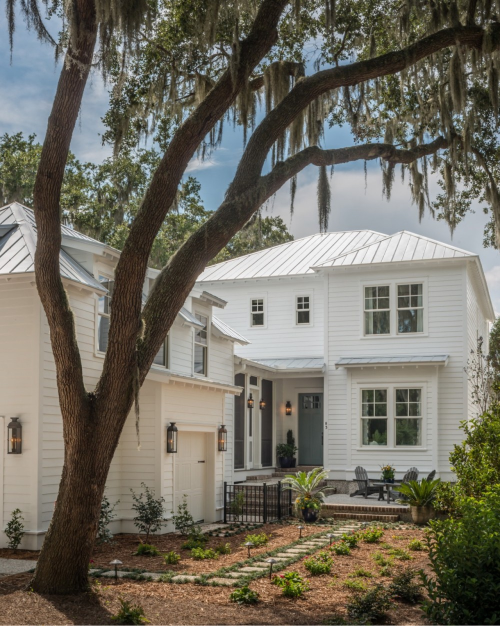 Deep eaves, exposed rafter tails, a metal roof for repelling heavy rains, and a tall live oak dripping with Spanish moss.