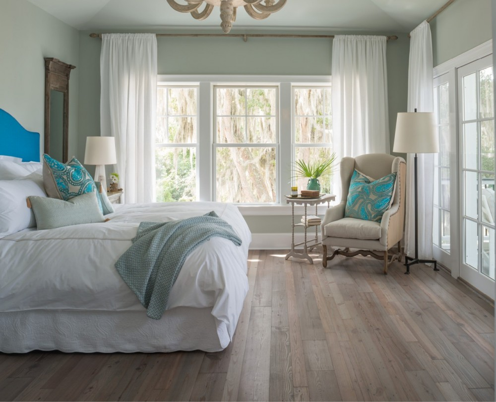 Soothing hues, softly weathered floors   and views of gauzy Spanish moss make the master bedroom a tranquil retreat.