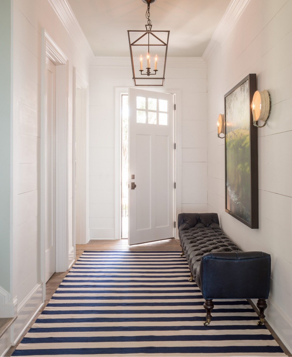 The entry hall's classic lighting, tufted bench and no-fuss rug set the tone for the relaxed elegance of the Mondavis' Low Country lifestyle.