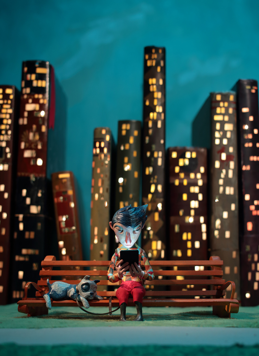 a fella sits with his dog on a park bench reading a device with a skyline of books make into skyscrapers.